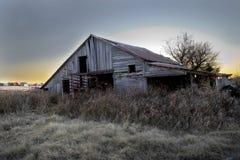 Por do sol atrás de um celeiro abandonado fotos de stock royalty free