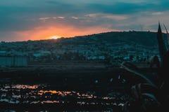 Por do sol atrás do monte povoado com reflexão imagem de stock royalty free