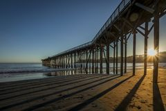 Por do sol através do cais de San Simeon Fotos de Stock Royalty Free
