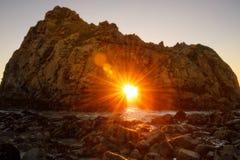 Por do sol através da praia de Pfeiffer do furo chave, Califórnia Imagem de Stock