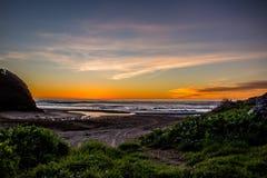 Por do sol através da ressaca pacífica A parte superior das ondas está sendo purga na frente do sol fotografia de stock