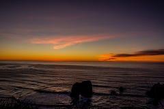 Por do sol através da ressaca pacífica A parte superior das ondas está sendo purga na frente do sol imagens de stock royalty free