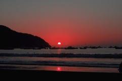 Por do sol avermelhado em Puerto López imagem de stock