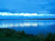 Por do sol azul sobre a água Imagem de Stock Royalty Free