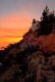 Por do sol baixo do farol do porto, porto da barra, Maine Imagem de Stock Royalty Free