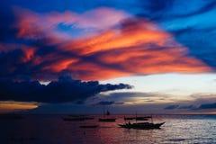 Por do sol bonito, colorido sobre barcos de pesca e povos na água Imagens de Stock