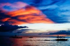 Por do sol bonito, colorido sobre barcos de pesca e povos na água Fotos de Stock
