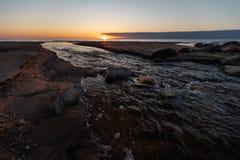 Por do sol bonito com água vermelha de um rio que retira ao mar - Veczemju Klintis da areia e de mola, Letónia - 13 de abril imagem de stock
