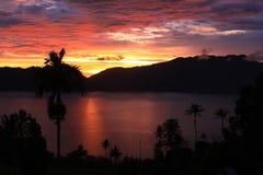 Por do sol bonito com as palmeiras na beira do lago Fotografia de Stock Royalty Free