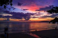 Por do sol bonito com cores vermelhas, roxas e amarelas na praia em Tailândia fotos de stock