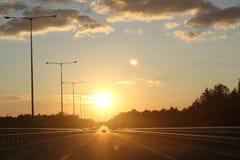 Por do sol bonito com a estrada das estradas do asfalto na cena rural Grandes nuvens no céu da noite fotos de stock