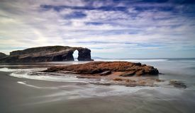 Por do sol bonito e arcos de pedra em Playa de las Catedrales, Espanha Imagem de Stock Royalty Free
