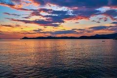 Por do sol bonito e mar com nuvens coloridas imagem de stock