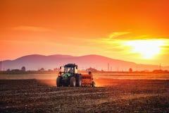 Por do sol bonito, fazendeiro no trator que prepara a terra com sementeira fotografia de stock