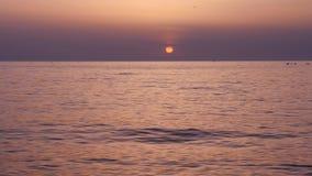 Por do sol bonito na praia com lentamente as ondas de rolamento video estoque