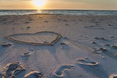 Por do sol bonito na praia com pilhas e os desenhos de madeira dos corações na areia fotos de stock royalty free