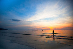 Por do sol bonito na praia do mar, silhueta nadadora das meninas Foto de Stock