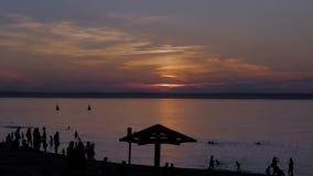 Por do sol bonito no banco de rio Silhuetas dos povos que jogam na praia vídeos de arquivo