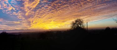 Por do sol bonito no campo com céu alaranjado imagens de stock royalty free