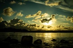 Por do sol bonito no lago as nuvens pequenas pequenas são coloridas no céu imagens de stock royalty free