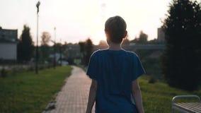 Por do sol bonito o menino anda ao longo da margem Luz bonita Sun bonito video estoque
