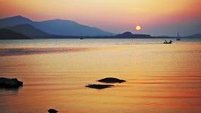 Por do sol bonito pelo mar e pelas montanhas no fundo Barcos que navegam no mar em por do sol surpreendente Movimento lento filme