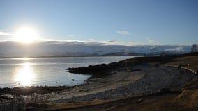 Por do sol bonito sobre a cordilheira nevado poderosa no círculo ártico com as ondas do céu azul e da calma e a costa arenosa video estoque
