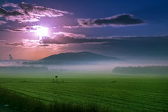 Por do sol bonito sobre o campo verde Imagens de Stock Royalty Free