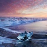Por do sol bonito sobre a praia famosa do diamante, Islândia Esta praia da lava da areia está completa de muitas gemas gigantes d foto de stock