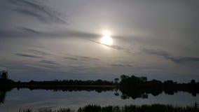 Por do sol bonito sobre um lago Imagem de Stock