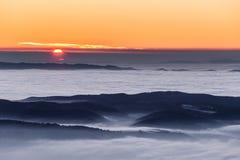 Por do sol bonito sobre um vale enchido pela névoa com as montanhas e os montes imagens de stock royalty free