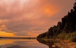 Por do sol borrado da nuvem sobre o lago e a linha costeira fotografia de stock