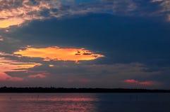 Por do sol cênico com o céu nebuloso alaranjado sobre um lago Fotos de Stock