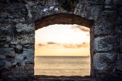 Por do sol cênico sobre o mar através da janela de ruínas velhas com opinião dramática do céu e de perspectiva com efeito da luz  Imagem de Stock