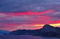Por do sol carmesim colorido na costa do Mar Negro em Crimeia, Sudak Imagens de Stock