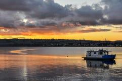 Por do sol colorido com um barco no lago Taupo, Nova Zelândia imagem de stock
