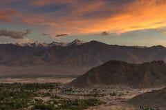 Por do sol colorido dramático com tampa das montanhas com neve e a cidade pequena abaixo do céu nublado dramático imagens de stock