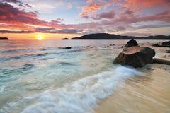 Por do sol colorido e onda de fluxo em uma praia. Fotos de Stock