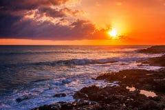 Por do sol colorido impressionante fantástico pelo mar, pelas ondas e pelo sunligh fotografia de stock
