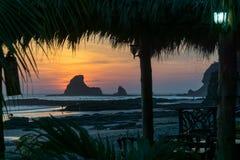Por do sol colorido na praia em Nicarágua com uma rocha e em leafes da banana na parte dianteira foto de stock