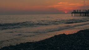 Por do sol colorido no mar Praia seixoso bonita com ondas e cais filme