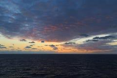 Por do sol colorido no oceano com nuvens cor-de-rosa fotografia de stock