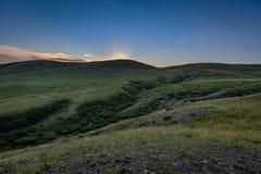 Por do sol colorido sobre montes verdes em Inner Mongolia imagens de stock royalty free