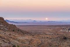 Por do sol colorido sobre o deserto de Namib, Aus, Namíbia, África Céu claro violeta do vermelho alaranjado no horizonte, nas roc imagem de stock