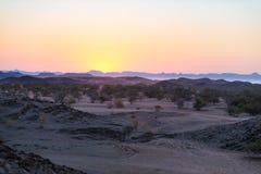 Por do sol colorido sobre o deserto de Namib, Namíbia, África Montanhas, dunas e de árvores da acácia silhueta no luminoso Clea d Imagem de Stock
