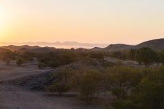 Por do sol colorido sobre o deserto de Namib, Namíbia, África Montanhas, dunas e de árvores da acácia silhueta no luminoso Clea d Fotos de Stock