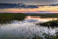 Por do sol colorido sobre o lago em Letónia imagem de stock royalty free