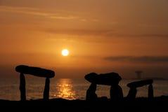 Por do sol com as pedras na praia Fotografia de Stock