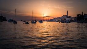 Por do sol com barcos e a cidade velha de Rovinj na Croácia fotos de stock