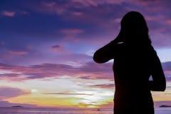 Por do sol com a menina da silhueta na praia fotografia de stock royalty free